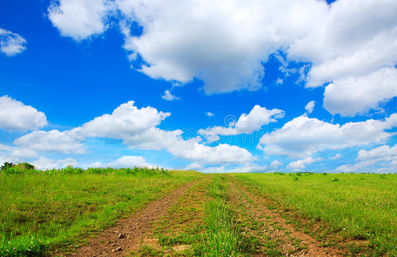 Coloque a estrada com grama verde e o céu azul com nuvens imagem de stock royalty free
