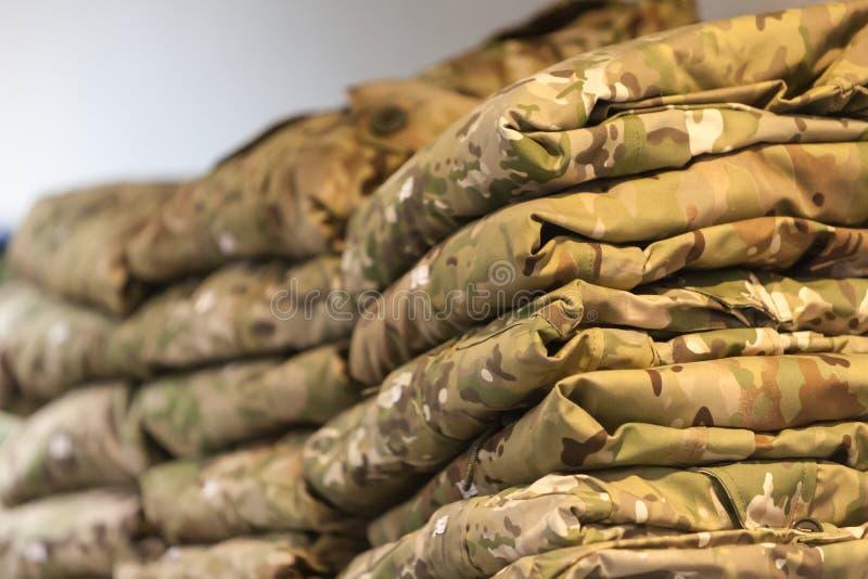 Coloque la ropa del camuflaje en el estante de una Warehouse-tienda especializada para la policía y los uniformes militares fotos de archivo