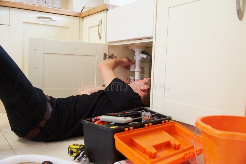 Coloque o encanador que fixa a banca da cozinha em uma casa imagem de stock royalty free