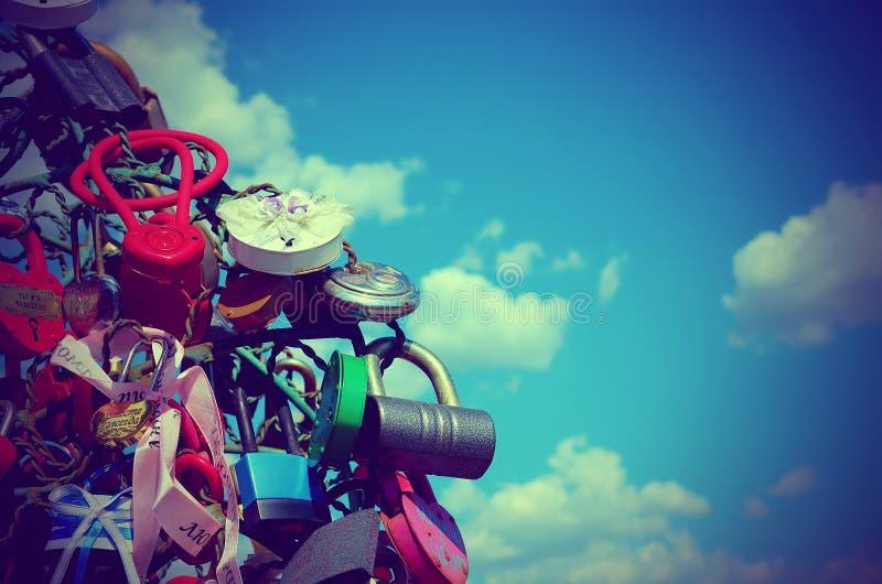 Coloré épouser ferme à clef contre le ciel bleu avec des nuages photographie stock