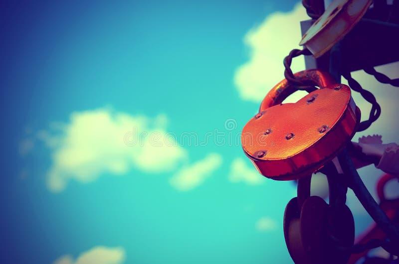Coloré épouser ferme à clef contre le ciel bleu avec des nuages photo stock