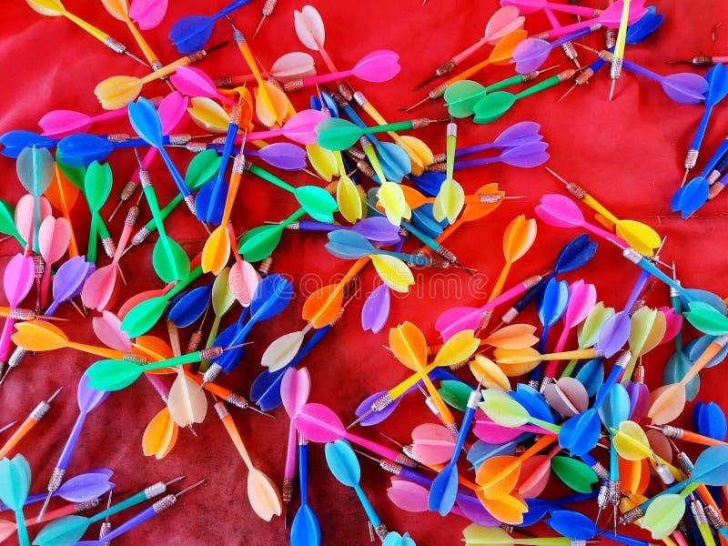 Coloré de beaucoup de dards sur le fond rouge image stock