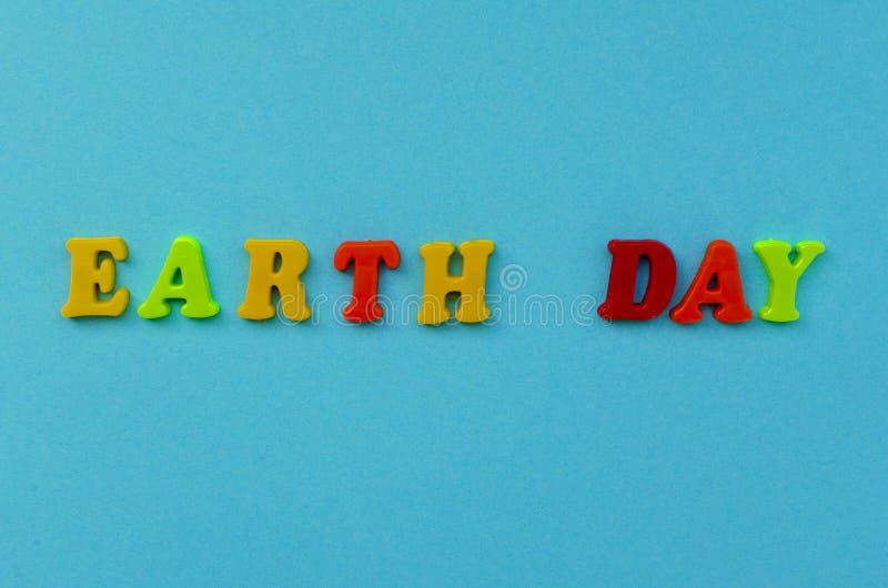 ` Coloré de jour de terre de ` des textes des lettres magnétiques sur le fond de papier bleu images stock