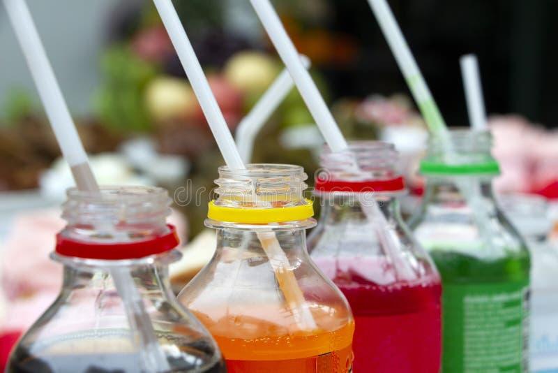 Coloré des bouteilles de soude carbonatées de bruit de boisson non alcoolisée avec la paille en plastique Bouteilles en plastique images stock