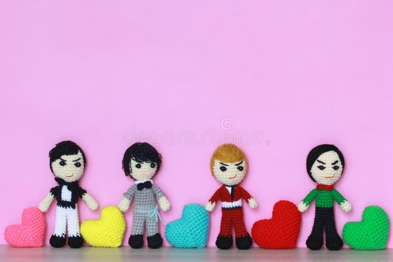 Coloré du coeur fait main de crochet et de la poupée de crochet sur le fond rose pour le jour de valentines images stock