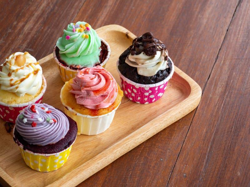 Coloré du petit gâteau fait maison dans le plateau en bois sur tableColorful en bois du petit gâteau fait maison dans le plateau  photos libres de droits