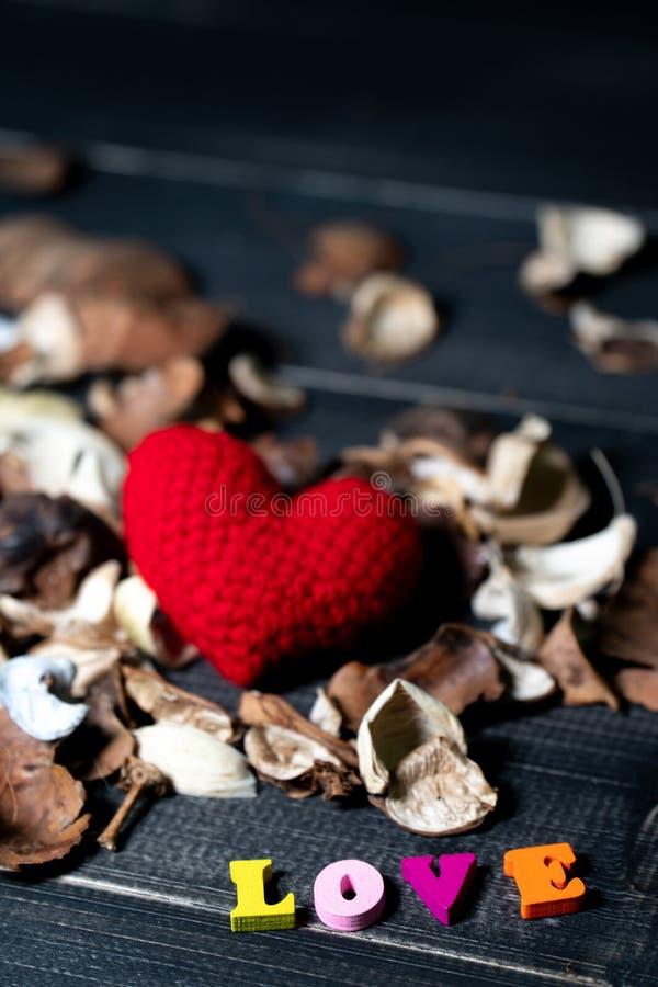 Coloré du texte en bois d'amour avec les fleurs et les feuilles sèches par arome bavardez le coeur rouge sur les fleurs sèches su photos stock