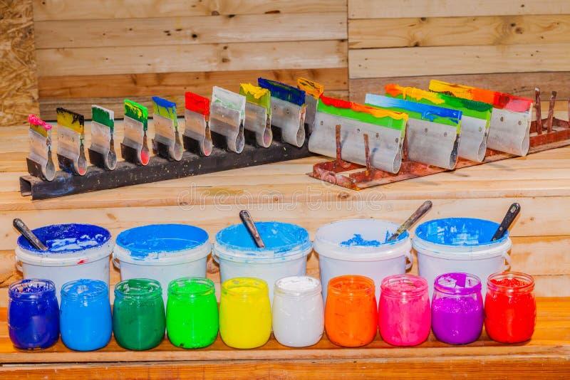 Coloré du verre d'encre de plastisol en clair pouvez sur la table de bois du pin pour le tee-shirt d'impression d'écran image libre de droits