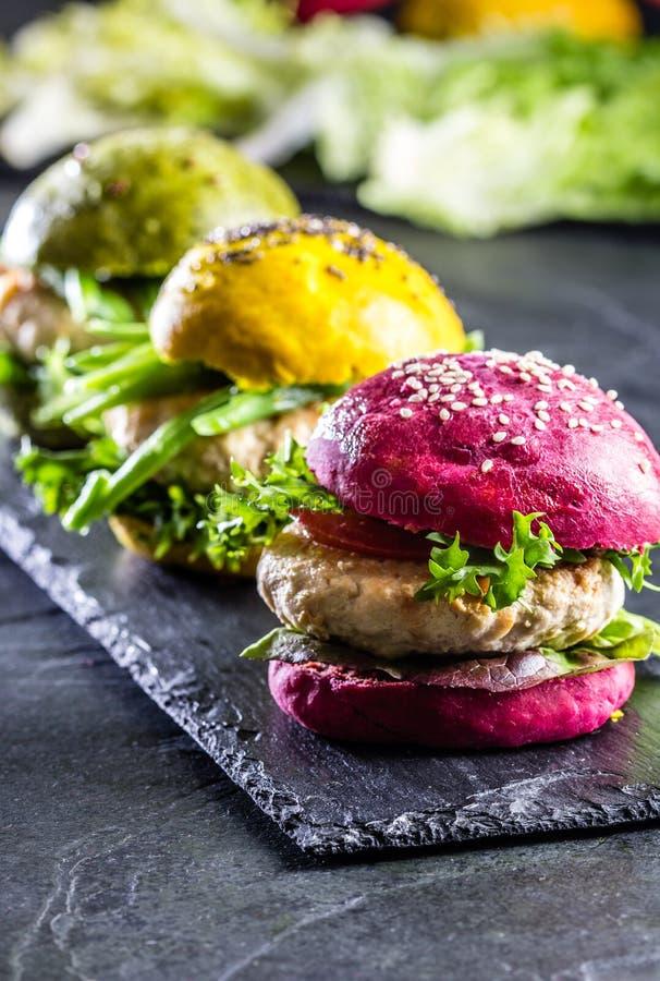 Coloré les hamburgers verts, jaunes et pourpres sur l'ardoise embarquent, slate le fond photo stock
