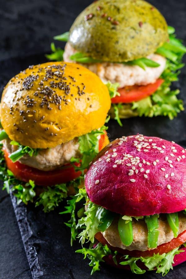 Coloré les hamburgers verts, jaunes et pourpres sur l'ardoise embarquent, slate le fond photographie stock libre de droits
