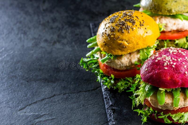 Coloré les hamburgers verts, jaunes et pourpres sur l'ardoise embarquent, slate le fond photographie stock