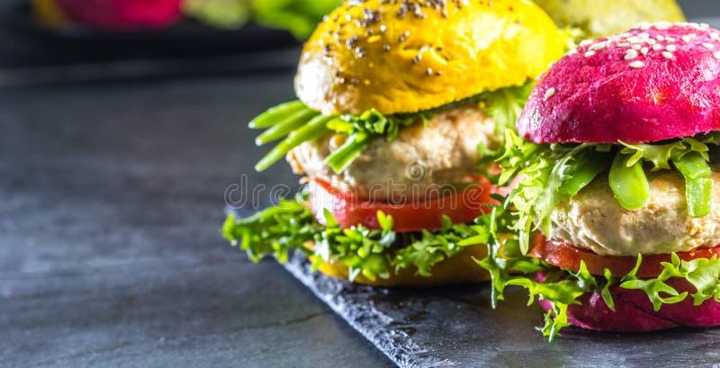 Coloré les hamburgers verts, jaunes et pourpres sur l'ardoise embarquent, slate le fond images libres de droits