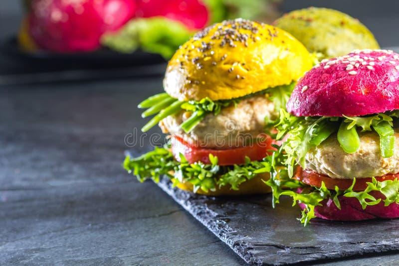 Coloré les hamburgers verts, jaunes et pourpres sur l'ardoise embarquent, slate le fond images stock