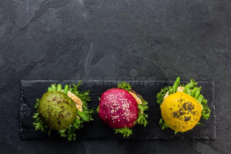 Coloré les hamburgers verts, jaunes et pourpres sur l'ardoise embarquent Vue supérieure photographie stock libre de droits