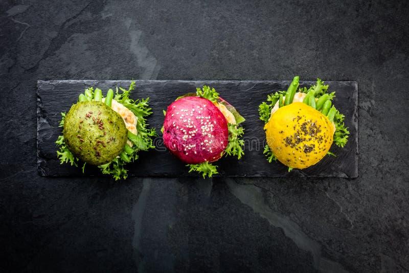 Coloré les hamburgers verts, jaunes et pourpres sur l'ardoise embarquent Vue supérieure images libres de droits