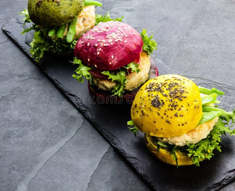 Coloré les hamburgers verts, jaunes et pourpres sur l'ardoise embarquent Vue supérieure image stock