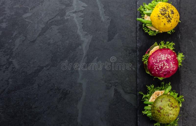 Coloré les hamburgers verts, jaunes et pourpres sur l'ardoise embarquent Vue supérieure photo stock