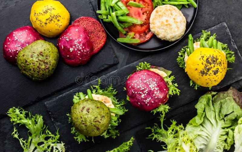 Coloré les hamburgers verts, jaunes et pourpres sur l'ardoise embarquent Vue supérieure photos libres de droits