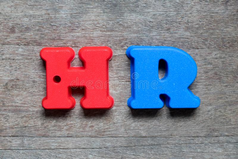Color alphabet in word HR abbreviation of Human resource. On wood background royalty free stock photo