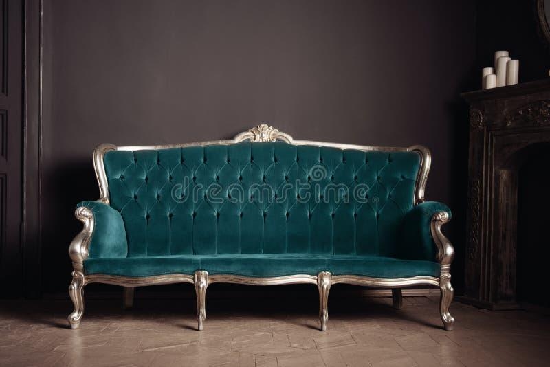 Color antiguo lujoso de la turquesa del sofá del velor cerca de la chimenea fotos de archivo