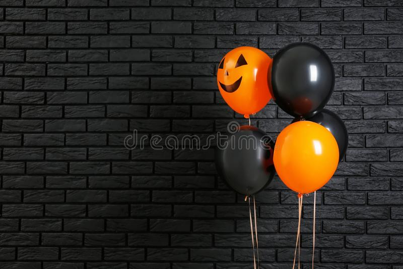 Color balloons for Halloween party on dark brick wall background stock photo