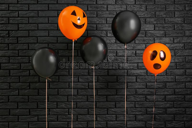 Color balloons for Halloween party on dark brick wall background royalty free stock images