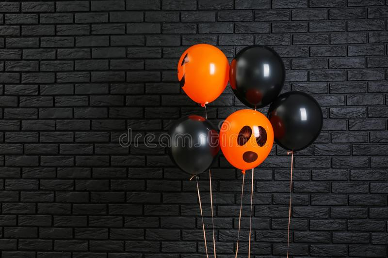 Color balloons for Halloween party on dark brick wall background stock image