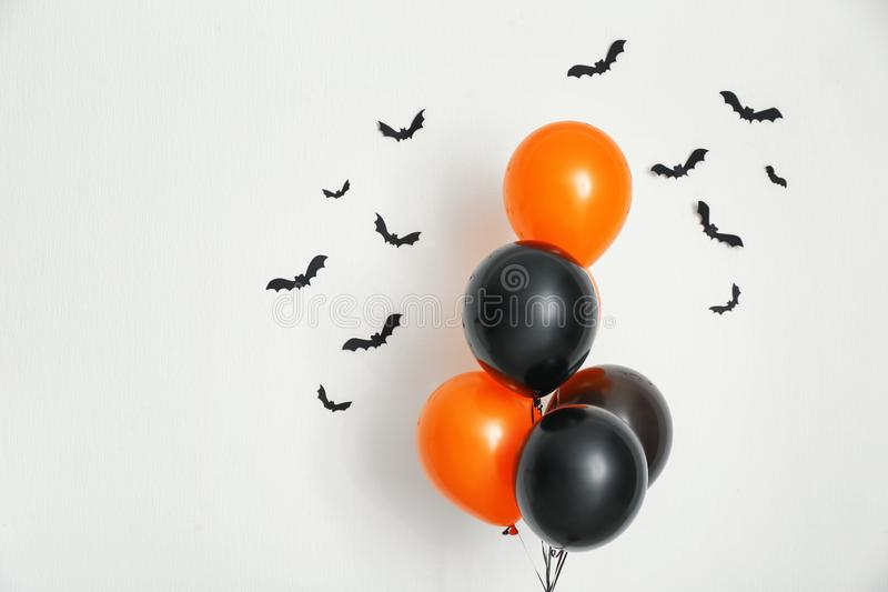 Color balloons with paper bats for Halloween party on light background stock images