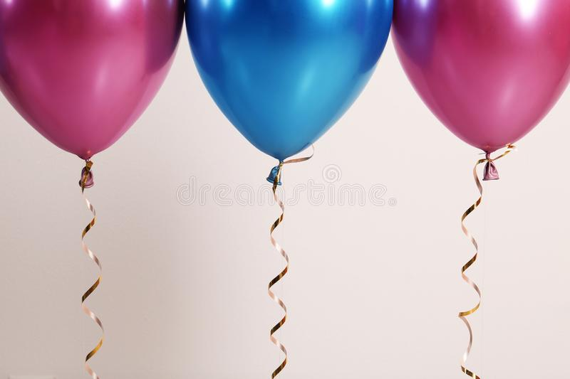 Color balloons with ribbons on white background, closeup. Space for text stock photos