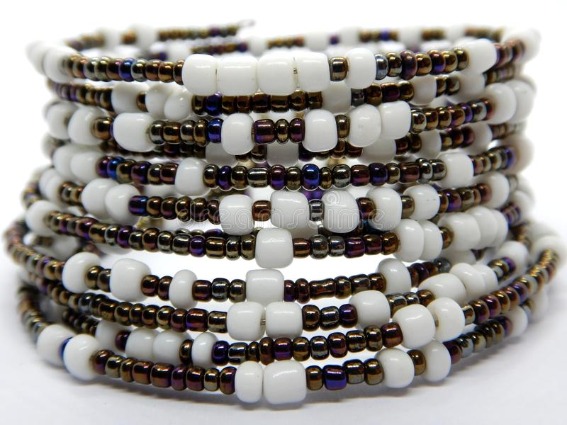 Color bead bracelet close-up, African handmade fashion jewelry. African handmade bead jewelry close-up, white and metal bead-spiral stock photos