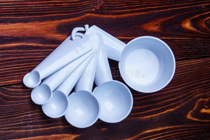 Color blanco plástico determinado de medición de las cucharas y de las tazas de la tabla en woode fotografía de archivo libre de regalías