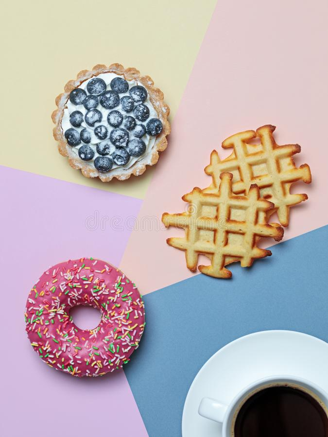 Color block flat lay with coffee, donut, tart and waffles. Flat lay with black coffee and delicious desserts - donut, blueberry tart and waffles - on pastel stock photos