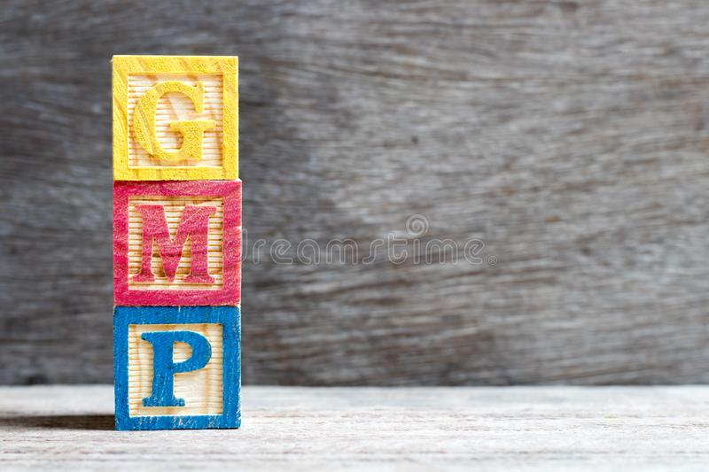 Color block in word GMP Abbreviation of good manufacturing practice on wood background. Color letter block in word GMP Abbreviation of good manufacturing stock photography