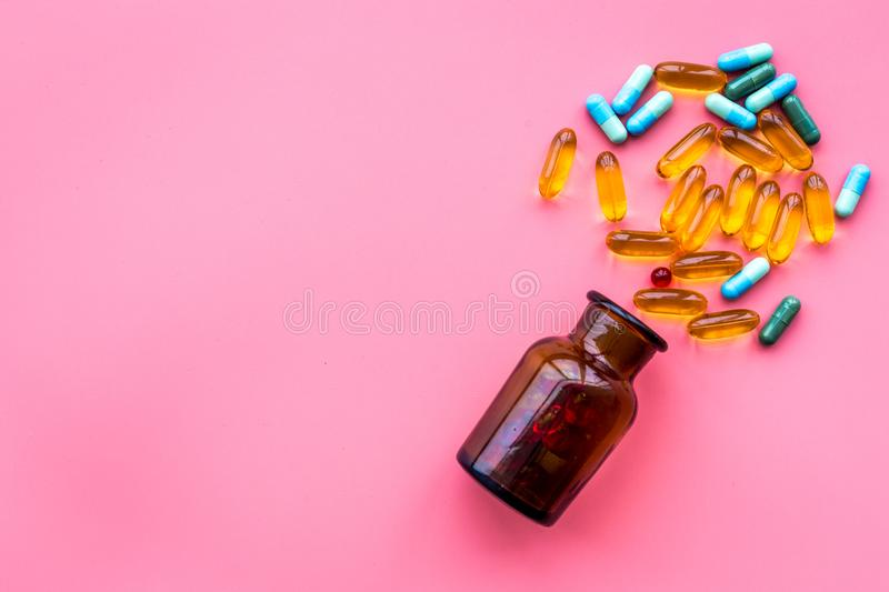Color blue and yellow pills spilling out of a pill bottle on pink background top view copy space stock image
