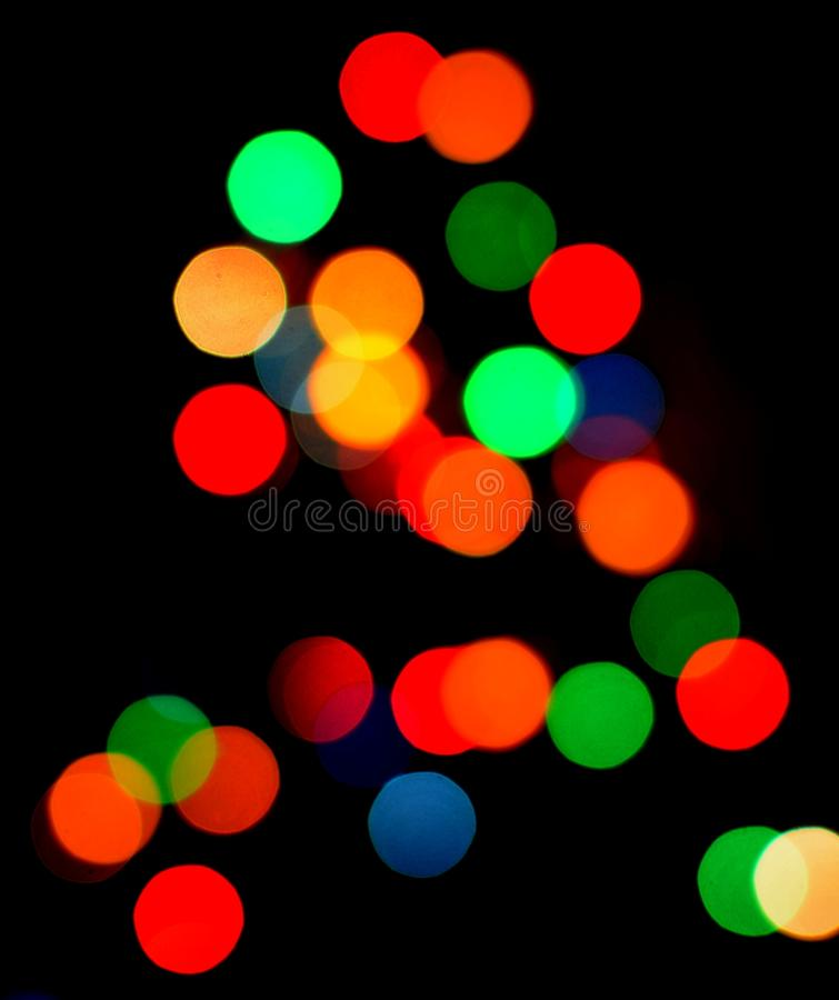 Color bokeh. Blurred multicolor shiny light bokeh on christmas tree royalty free stock images