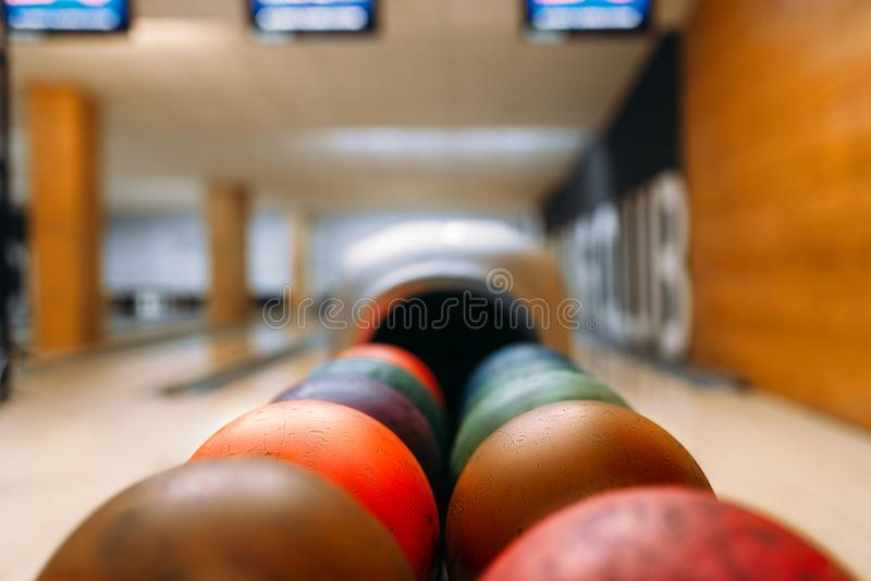 Color bowling balls in feeder, bowl game concept. Color bowling balls in feeder, lane with pins on background, nobody. Bowling game concept royalty free stock image