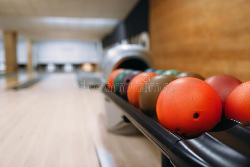 Color bowling balls in feeder, bowl game concept. Color bowling balls in feeder, lane with pins on background, nobody. Bowl game concept royalty free stock photos