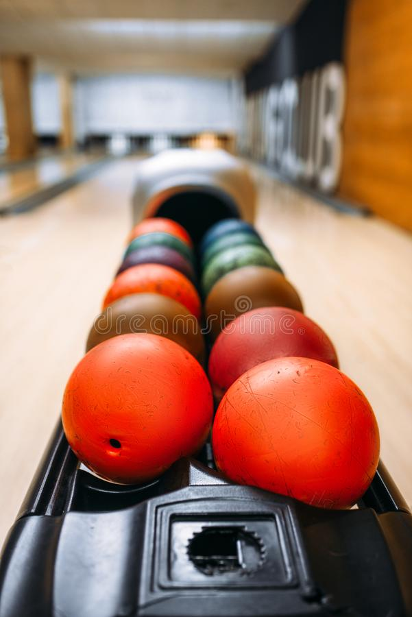 Color bowling balls in feeder, bowl game concept. Color bowling balls in feeder, lane with pins on background, nobody. Bowling game concept stock image