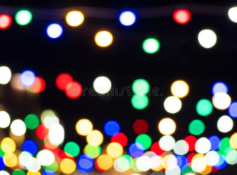 Color bright light spots on black background. Defocused street lights stock images