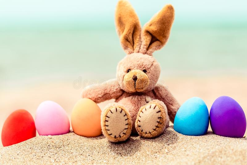 Easter bunny and color eggs on the sandy beach by. Color bunny easter eggs background small beautiful stock images