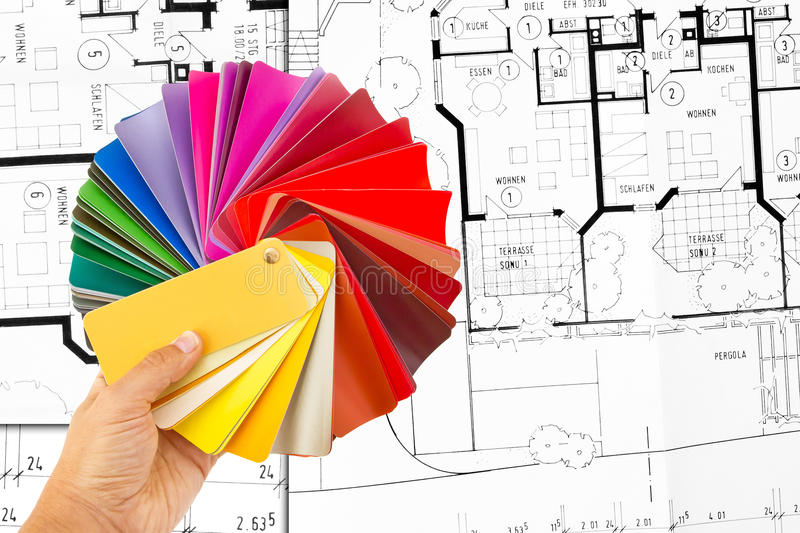 Color cart in hand. Man holding a set of paint color swatches in all the colors of the spectrum splayed out in his hand. In background a construction plan stock image