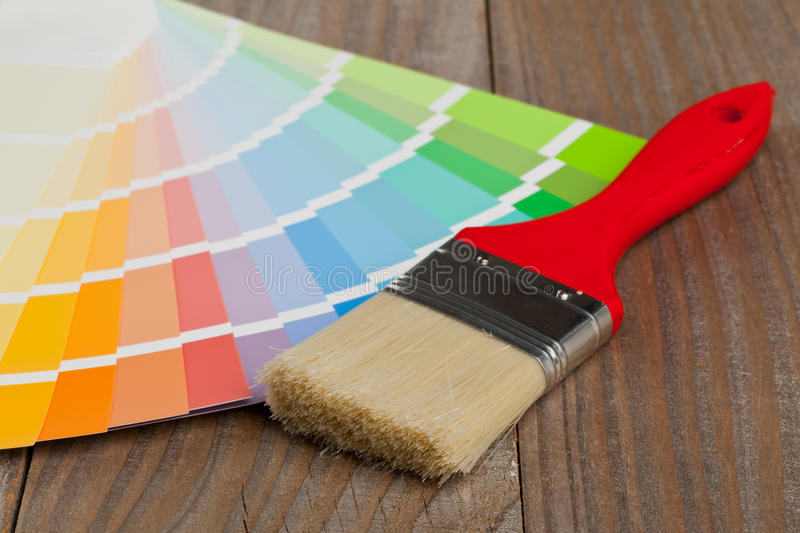 Color chart guide with brush. Color chart guide for renovation with brush on wooden surface stock photo