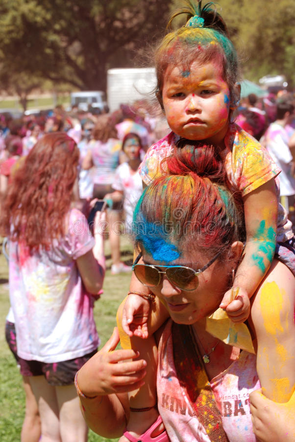 A Color coated toddler and Mom Spring Festival. The Holi Spring (color) Festival on the Austin Texas UT Campus, a rainbow powdered Mom with her color coated royalty free stock photo