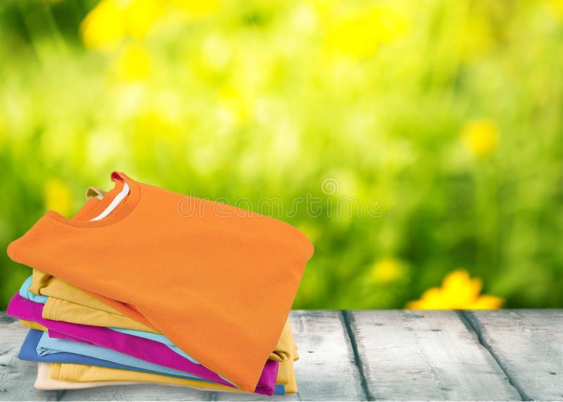 Stack of colorful t-shirts on wooden table with royalty free stock images