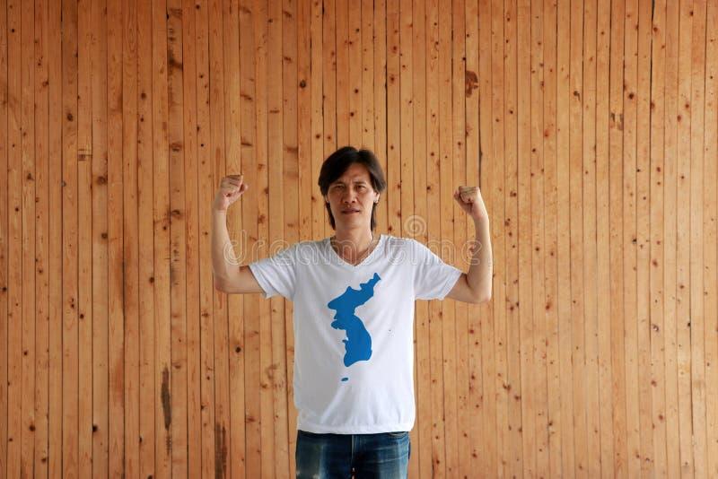 Color de la bandera de Corea de la unificación del hombre que lleva de la camisa y de la situación con el puño aumentado en el fo imagen de archivo libre de regalías
