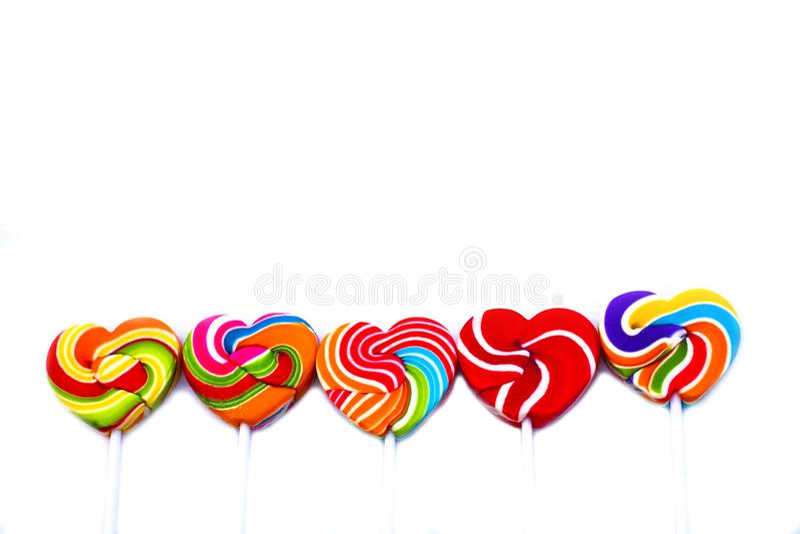 Color de la forma del corazón de los caramelos de los dulces lleno en el fondo blanco, caramelo determinado de las piruletas del  imágenes de archivo libres de regalías