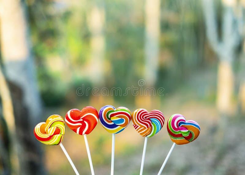 Color de la forma del corazón de los caramelos de los dulces lleno en el fondo borroso, caramelo determinado de las piruletas del fotos de archivo