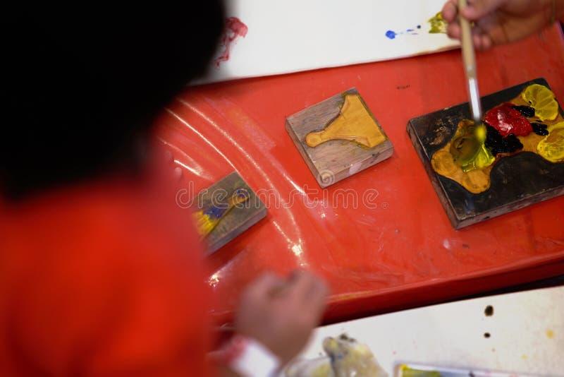 color de las manos del niño en la placa para hacer el bombeo o el sellado de las ilustraciones fotos de archivo