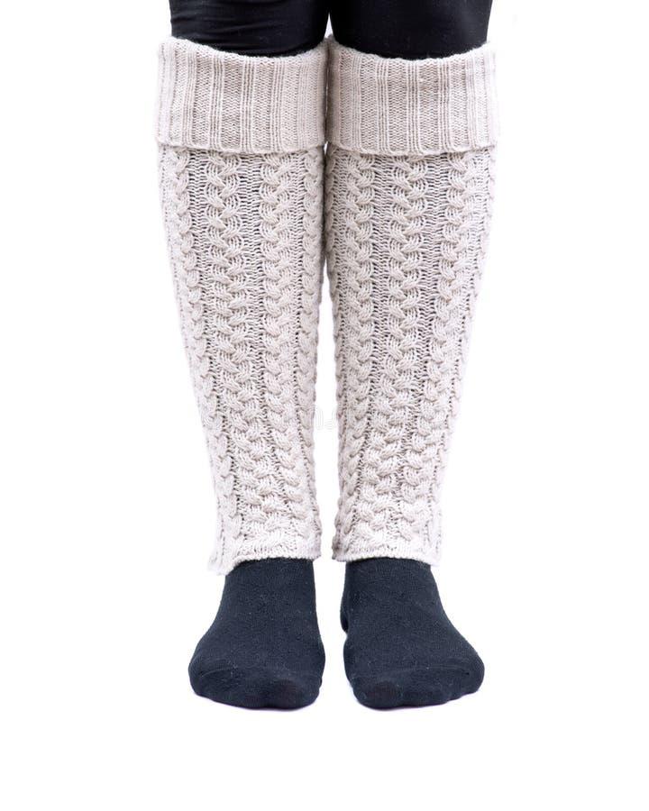 Color de marfil de los calentadores de la pierna del tejido en cable de la mujer que lleva joven aislado en blanco foto de archivo