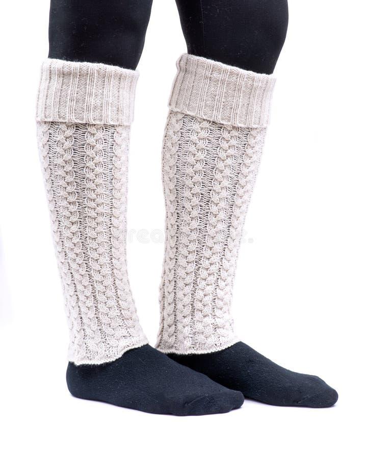 Color de marfil de los calentadores de la pierna del tejido en cable de la mujer que lleva joven aislado en blanco imagen de archivo libre de regalías